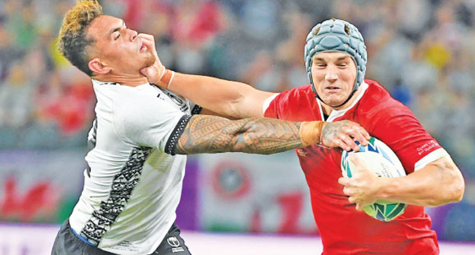 Brilliant Adams grabs hat-trick as battered Wales reach quarters